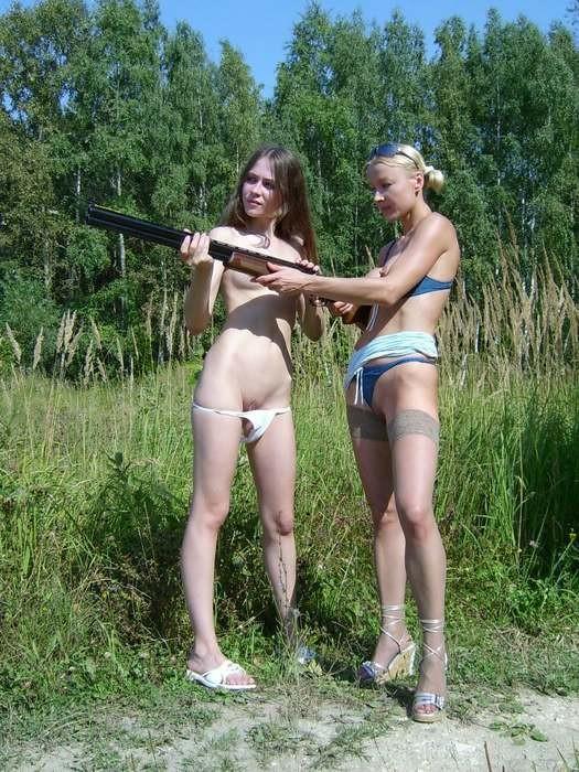 Две голые девушки позирует в лесу с ружьем