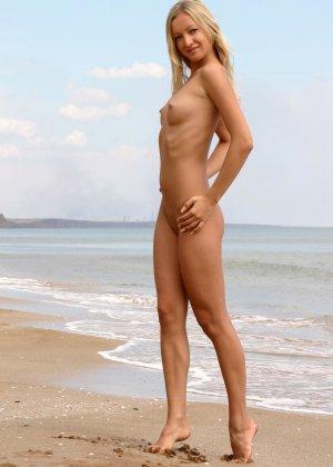 Красивая блондинка показывает стройную фигуру, плескаясь на море и выходя на нежный песок - фото 4