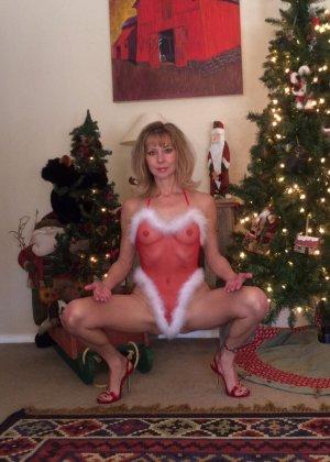 Девушка в рождественском боди позирует перед камерой – она выглядит достаточно соблазнительно - фото 12