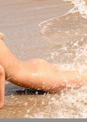 Красивая блондинка показывает стройную фигуру, плескаясь на море и выходя на нежный песок - фото 12