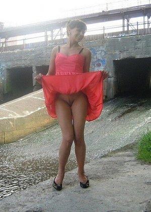 Девушка гуляет в летнем платье и периодически приподнимает его, чтобы показать свою киску - фото 2