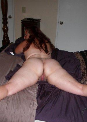 Развратница с аппетитной попкой показывает свой зад, широко расставляя ноги перед камерой - фото 1