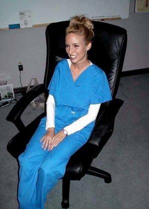 Сексуальная медсестра снимает с себя медицинский костюм и показывает силиконовую грудь - фото 1