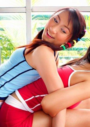 Две азиатки лесбиянки с в зале с большими мячами трогают волосатые вагины друг друга и ласкают розовые щели пальцами - фото 9