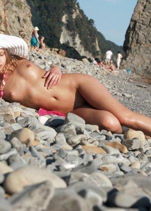 Красивая эротика, соло худой девушки на каменистом пляже, девка стыдливо прикрывает промежность - фото 13