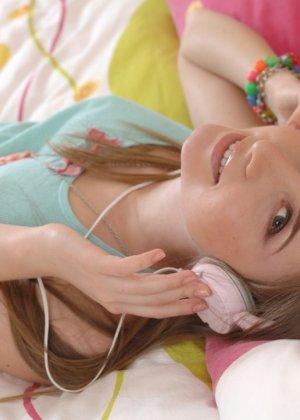 Милая девушка слушает музыку в наушниках и раздевается со скуки - фото 10