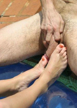 Сисястая телка лежит на матрасе в бассейне, парень лижет ей пальцы ног, дрочит ногами девушки и кончает на них - фото 15