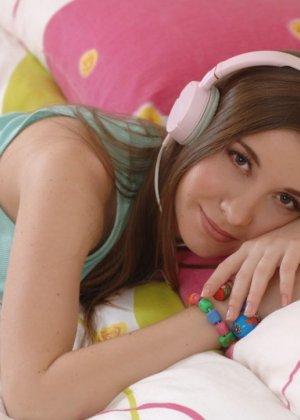 Милая девушка слушает музыку в наушниках и раздевается со скуки - фото 7
