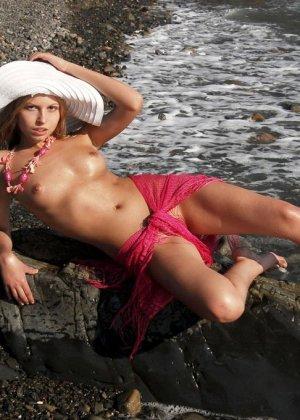 Красивая эротика, соло худой девушки на каменистом пляже, девка стыдливо прикрывает промежность - фото 3