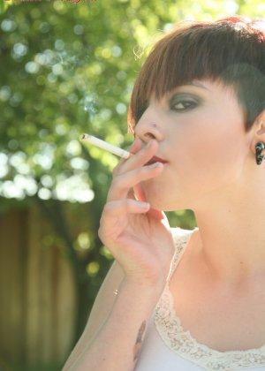 Морна вышла покурить, но пока она курит, еще и показывает сиськи и спускает трусы, демонстрируя пизду на улице - фото 11