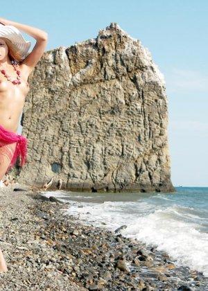 Красивая эротика, соло худой девушки на каменистом пляже, девка стыдливо прикрывает промежность - фото 20