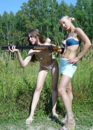 Две голые девушки позирует в лесу с ружьем - фото 13