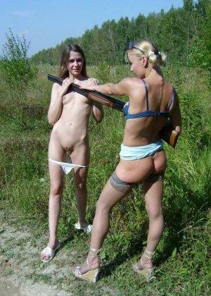 Две голые девушки позирует в лесу с ружьем - фото 3