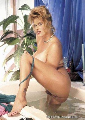 Пухлая зрелая домохозяйка в чулках забирается в ванну, ее одежда мокрая, но ее это не смущает, она играет со своими большими буферами - фото 1