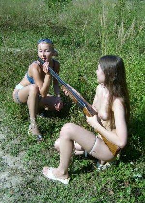 Две голые девушки позирует в лесу с ружьем - фото 6