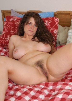 Женщина разделась на своей кровати, показав лохматую пизденку - фото 1