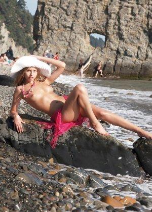 Красивая эротика, соло худой девушки на каменистом пляже, девка стыдливо прикрывает промежность - фото 2