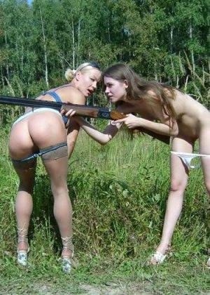 Две голые девушки позирует в лесу с ружьем - фото 4