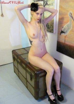 Худенькая блондинка с татуировками показывает свое тело, вылезая из огромного чемодана - фото 5