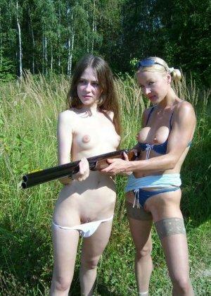 Две голые девушки позирует в лесу с ружьем - фото 16