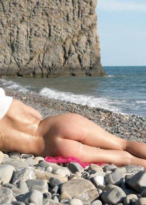 Красивая эротика, соло худой девушки на каменистом пляже, девка стыдливо прикрывает промежность - фото 17