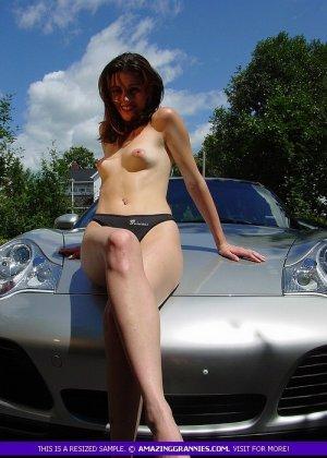 Молодая женщина показывает свою маленькую грудь, облокатившись на капот спортивного авто - фото 1