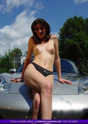 Молодая женщина показывает свою маленькую грудь, облокатившись на капот спортивного авто - фото 12
