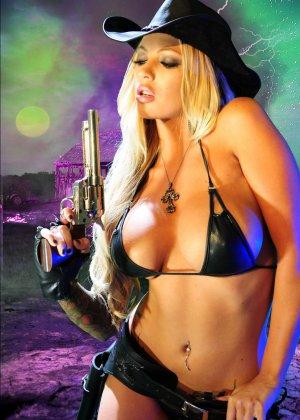 Меган Дэниэлс позирует с пистолетом и ружьем - фото 9