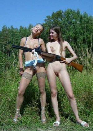 Две голые девушки позирует в лесу с ружьем - фото 10