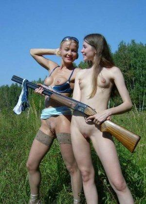 Две голые девушки позирует в лесу с ружьем - фото 12