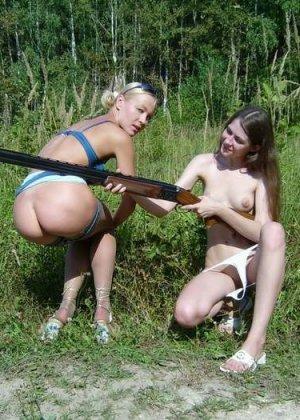 Две голые девушки позирует в лесу с ружьем - фото 5