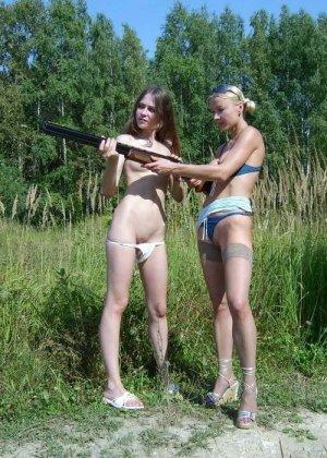 Две голые девушки позирует в лесу с ружьем - фото 15