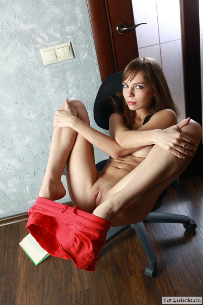 Худая девушка показывает бритую пизду на стуле