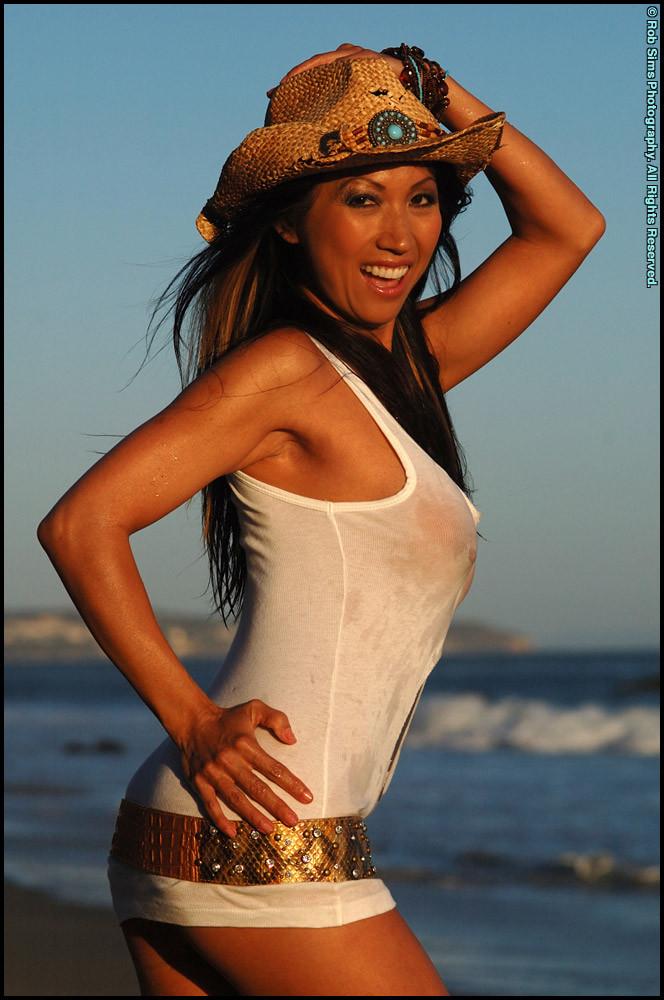 Голая женщина в ковбойской шляпе на пляже