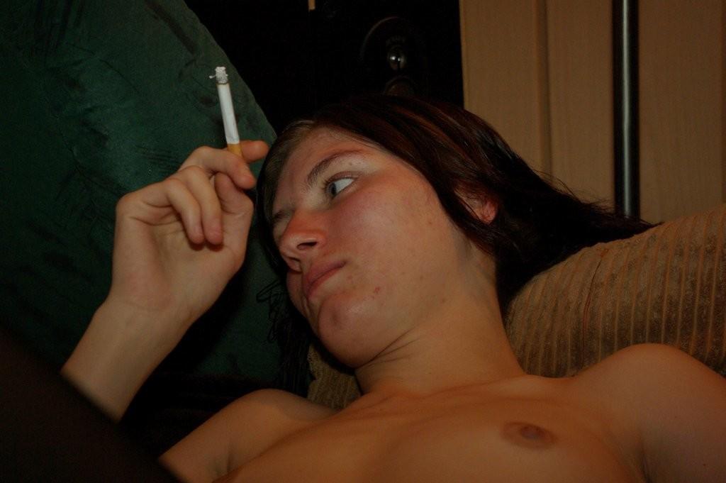Голенькая брюнеточка закурила сигарету в постели