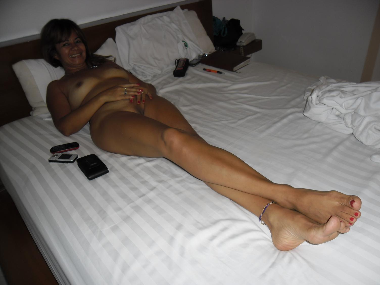 Голенькая длинноногая бабенка лежит на кроватке и показывает тело