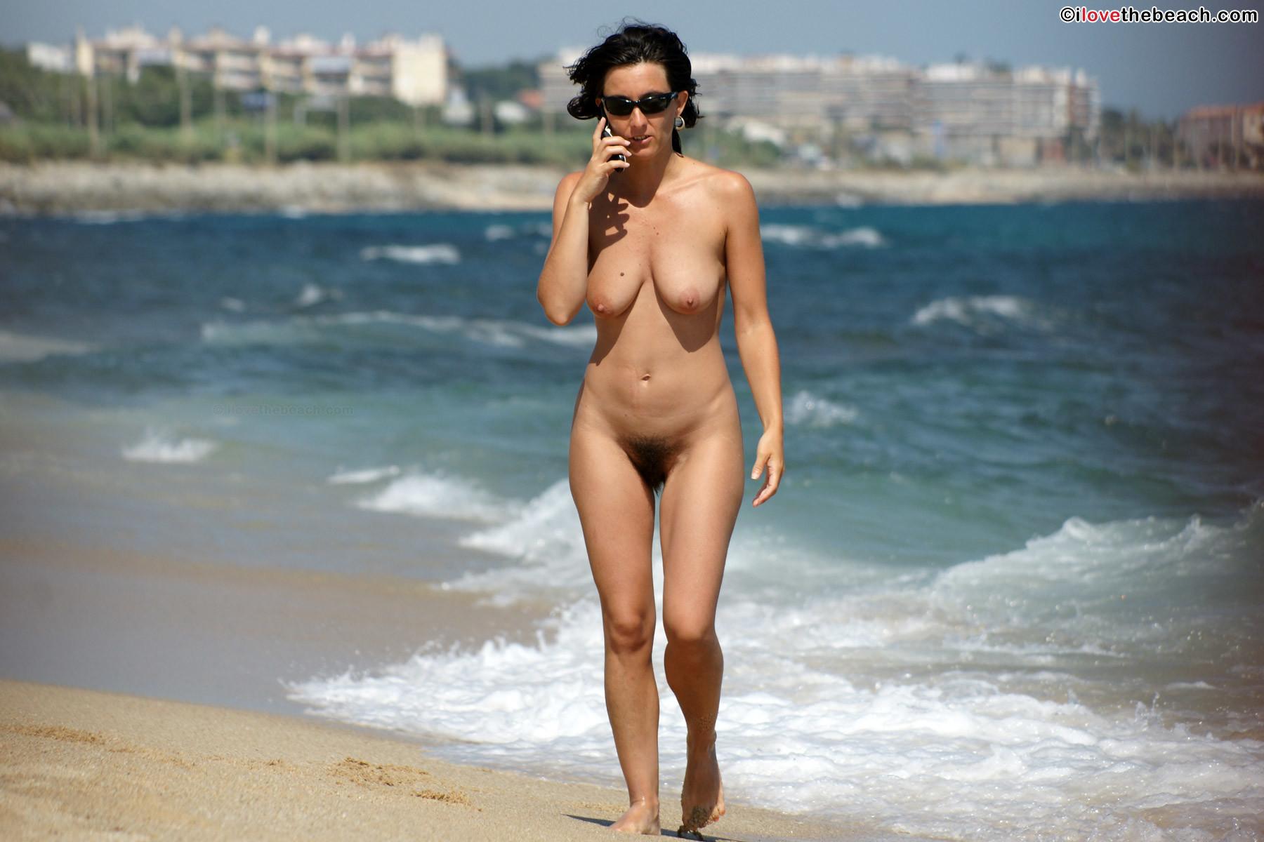 Раскованная девушка гуляет по пляжу абсолютно обнаженная