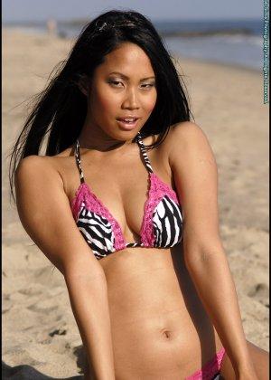 Азиатка снимает купальник на пляже - фото 8
