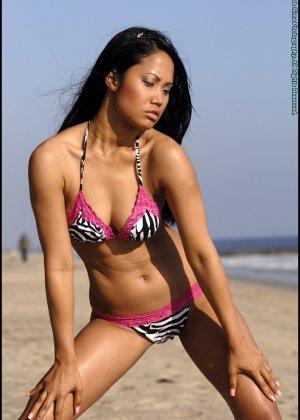 Азиатка снимает купальник на пляже - фото 3