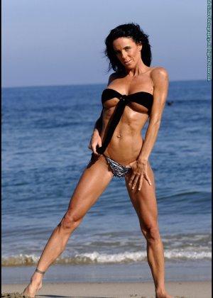 Женщина в мини купальнике на море - фото 4