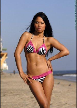 Азиатка снимает купальник на пляже - фото 1