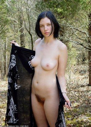 Голая брюнетка с волосатой вагиной позирует в лесу - фото 1