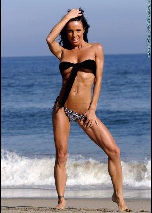 Женщина в мини купальнике на море - фото 5