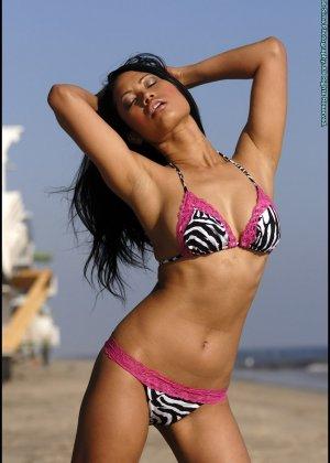 Азиатка снимает купальник на пляже - фото 2