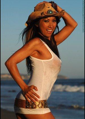 Голая женщина в ковбойской шляпе на пляже - фото 6