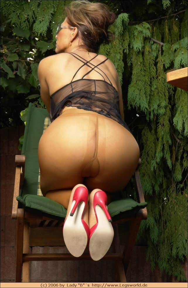 Длинноногая женщина в чулках позирует в саду