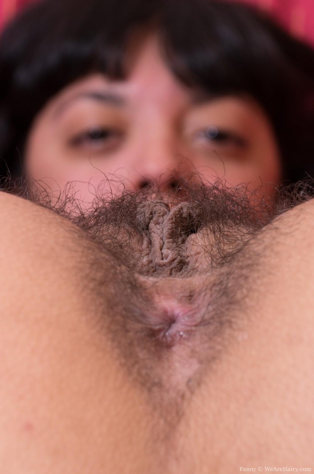 Глазастая брюнетка лежа на кровати показывает мохнатую щель