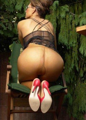 Длинноногая женщина в чулках позирует в саду - фото 5