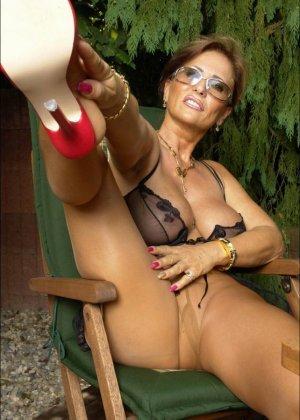 Длинноногая женщина в чулках позирует в саду - фото 3