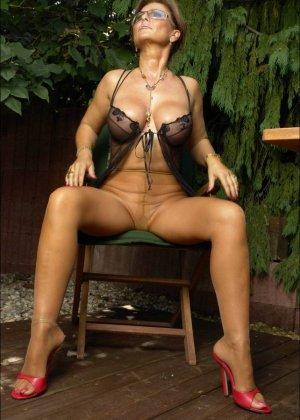 Длинноногая женщина в чулках позирует в саду - фото 4